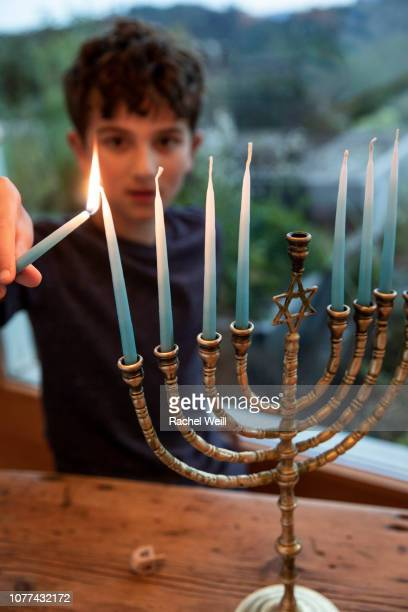 boy lighting candle on menorah - dreidel stock photos and pictures
