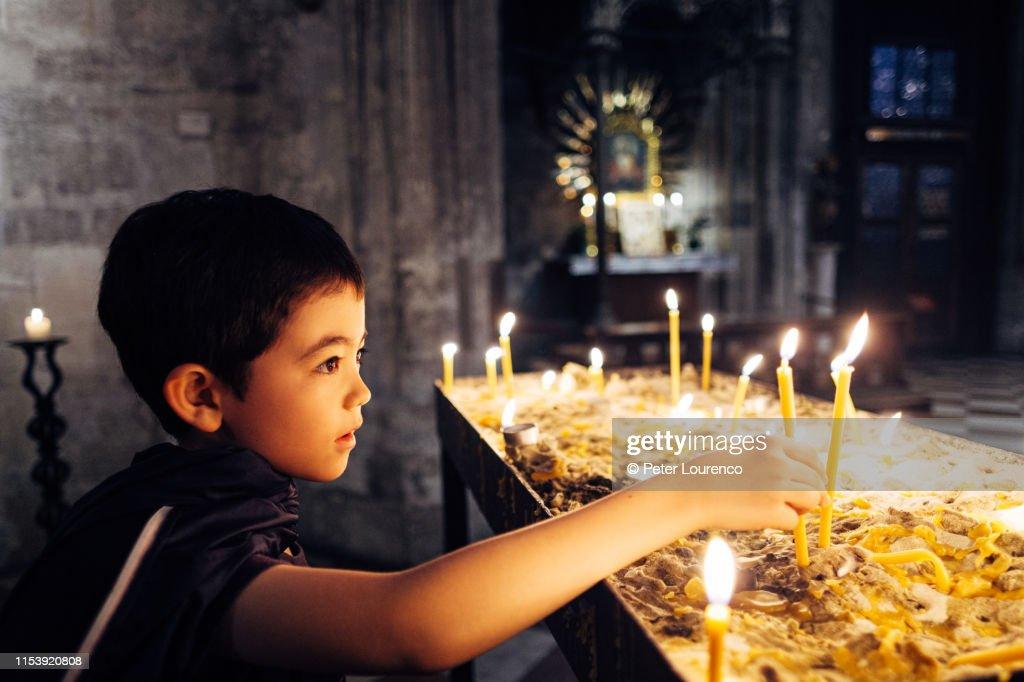 Boy lighting prayer candles : Stock Photo