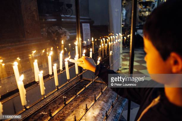boy lighting prayer candles - peter lourenco stock pictures, royalty-free photos & images