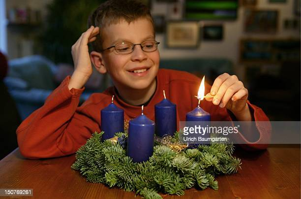 Boy lightning the first candle of an Advent wreath