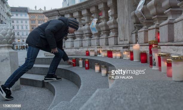 Boy lights a candle at the plague column in Vienna's city center on March 25, 2020. - People placed candles as a sign of hope against the corona...