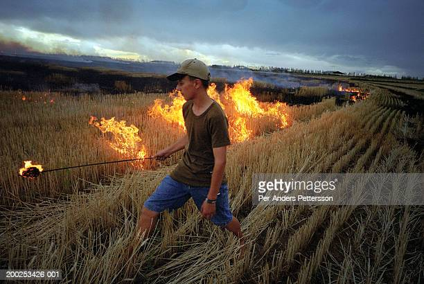 Boy lights fire in his father?s wheat fields in Orania, South Af