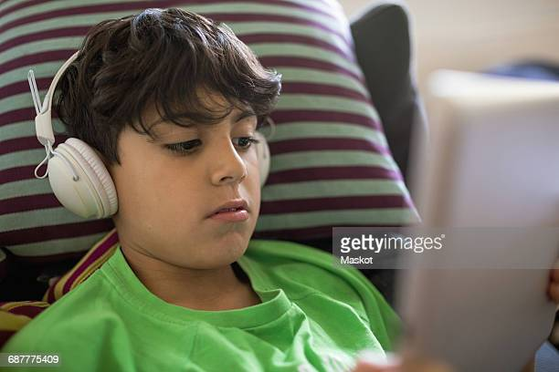 Boy listening music through digital tablet at home