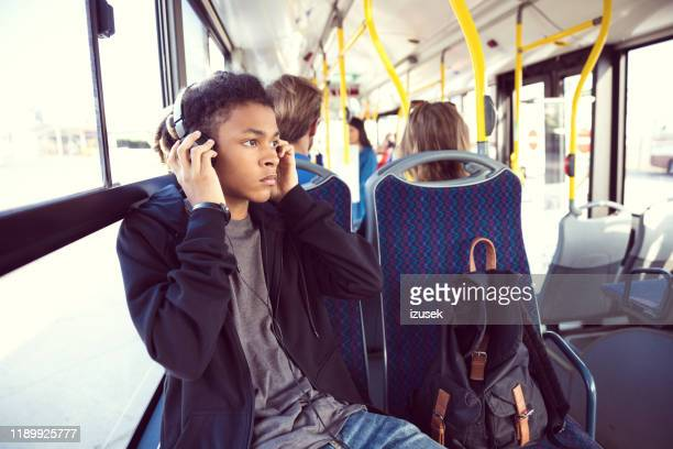 boy listening music while traveling in bus - bus stock pictures, royalty-free photos & images