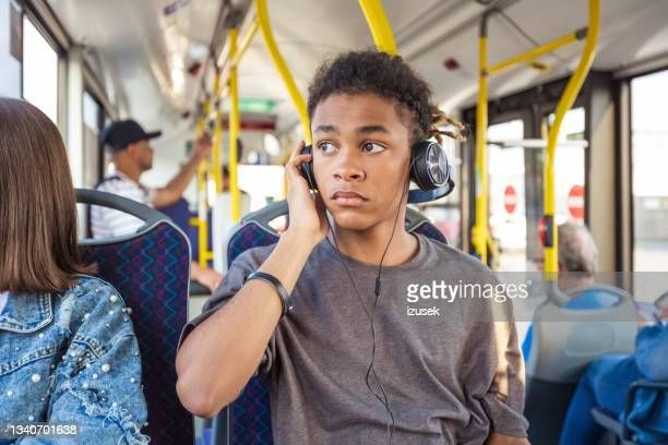 boy listening music while traveling in bus - izusek stock pictures, royalty-free photos & images