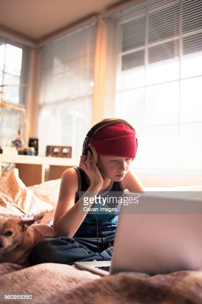 Boy listening music with headphones while using laptop on bed