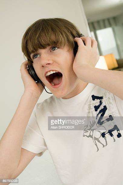 Boy listening to headphones and shouting