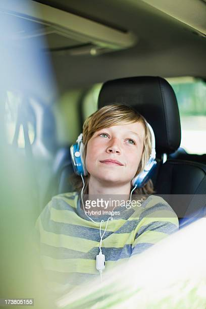Boy listening to headphones in car