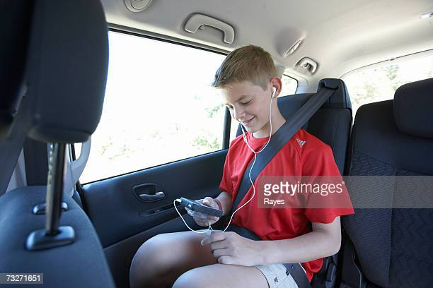 Boy (11-13) listening to mp3 player in car