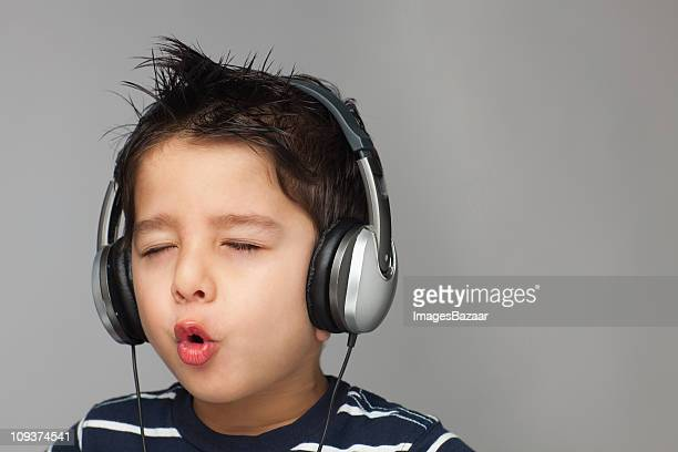 Boy (4-5) listening to music and singing