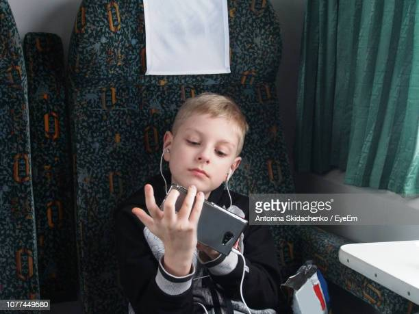 Boy Listening To Music Through In-Ear Headphones In Train