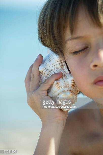 Boy listening to seashell with eyes closed