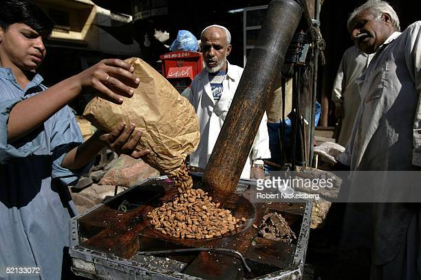 A boy loads almonds for crushing into an old style wooden mortar and pestle in Jodhia Bazaar old Karachi Pakistan January 28 2005 Karachi is one of...
