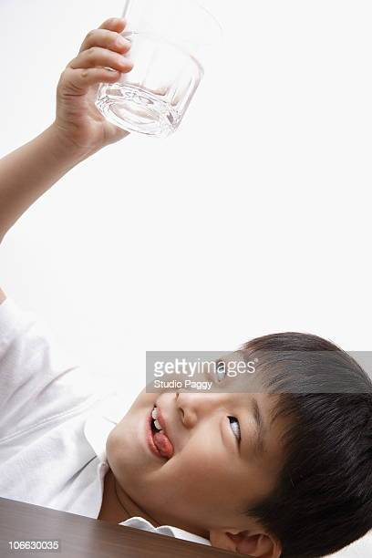 Boy looking a glass of water from bottom