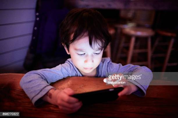 boy looking a mobile phone - only boys photos stock photos and pictures