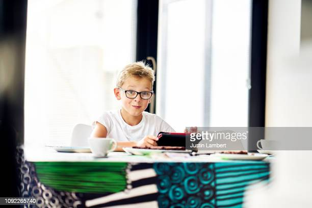 boy looking and smiling at camera while using his digital tablet at the kitchen table - saltdean stock pictures, royalty-free photos & images