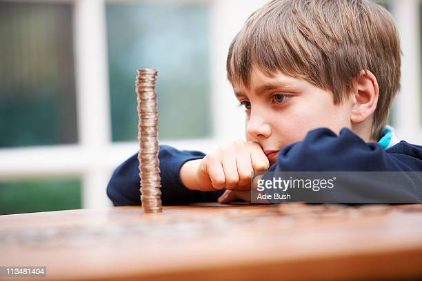 Boy looking at a tower of coins