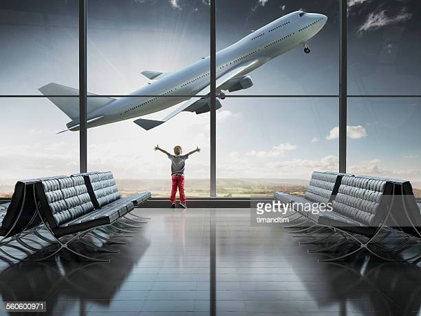 Boy looking at airplane taking off in airport term