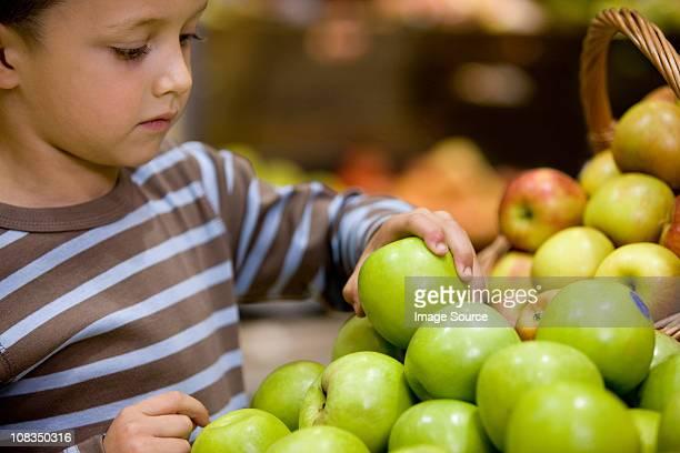 Boy looking at apples