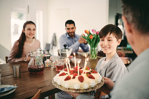 Boy looking at birthday cake while sitting with family at home - gettyimageskorea