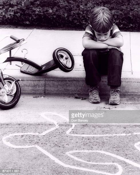 Boy (3-5) looking at body outline, damaged bicycle by side (B&W)