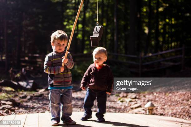 boy looking at brother holding artificial fish in playground - fish love stock pictures, royalty-free photos & images