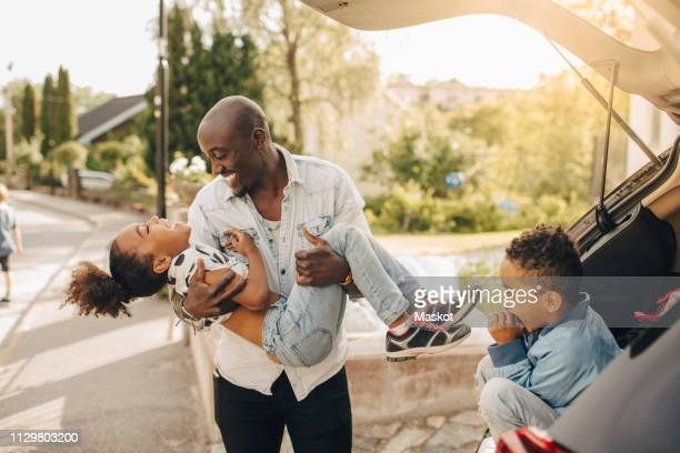boy looking at cheerful father carrying daughter by electric car on driveway - family and happiness and diverse stock photos and pictures
