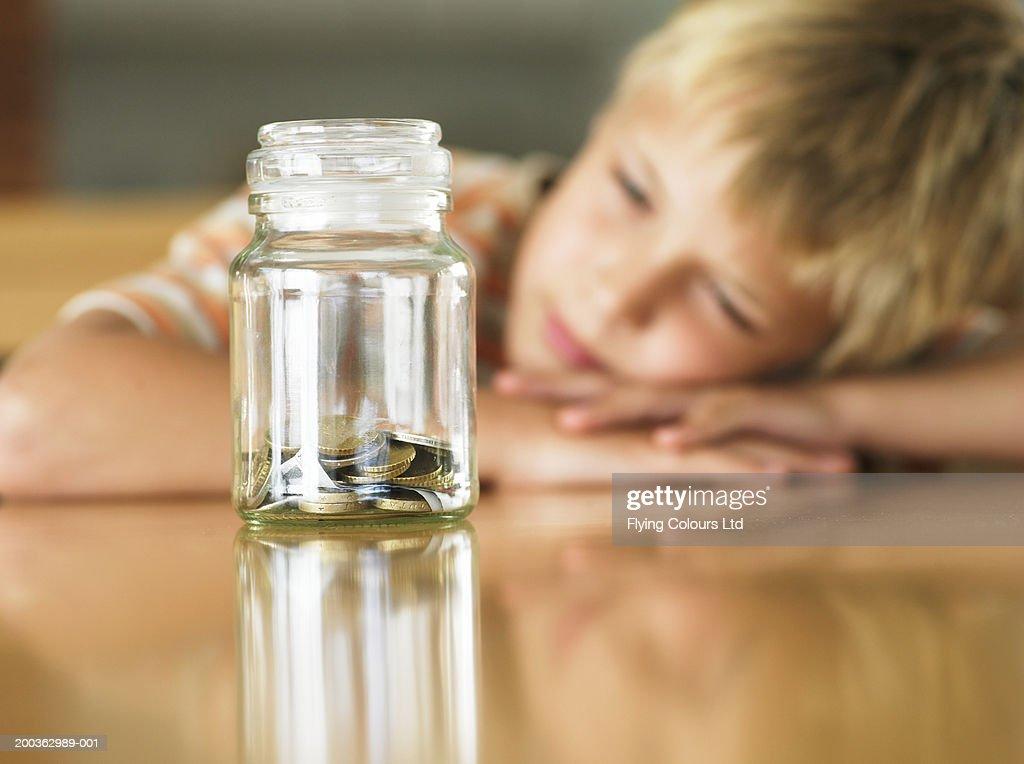 Boy (7-9) looking at coins in jar (focus on jar) : Stock Photo