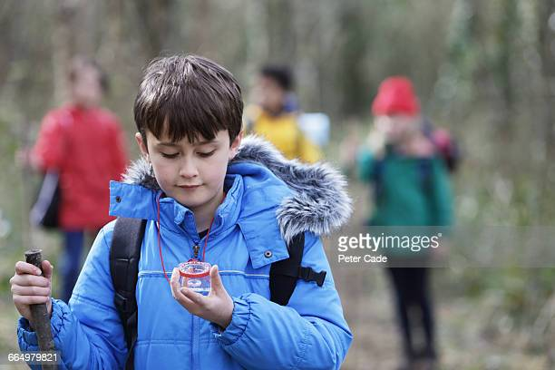 Boy looking at compass, leading group of friends