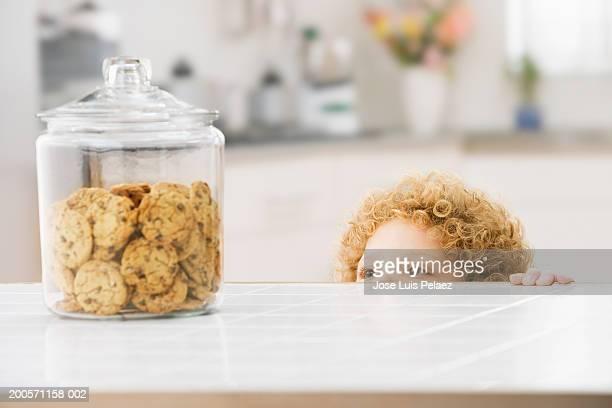 Boy (4-5) looking at cookie jar, close-up