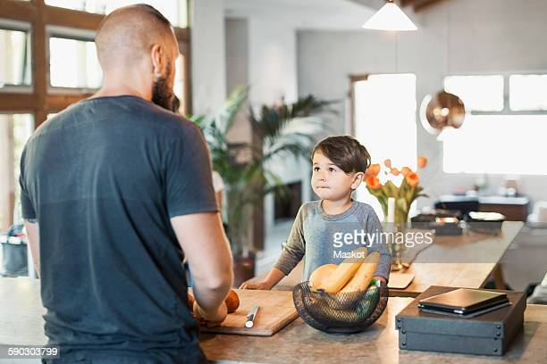 Boy looking at father standing at kitchen counter
