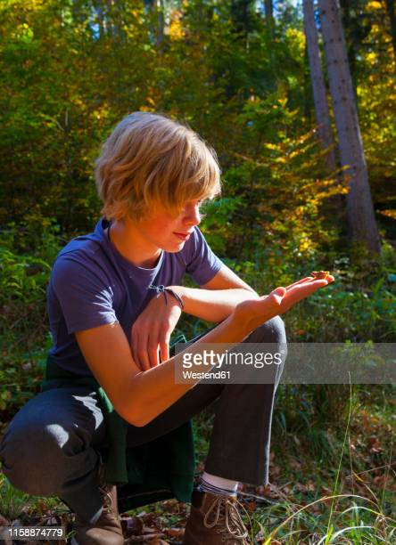 Boy looking at frog in hand