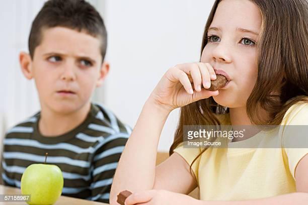 Boy looking at girl eating chocolate bar