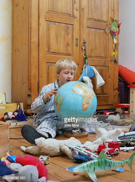 Boy (6-8) looking at globe in bedroom