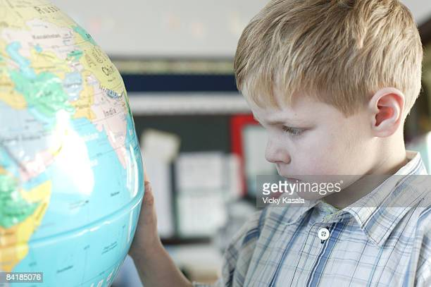 boy looking at globe in classroom