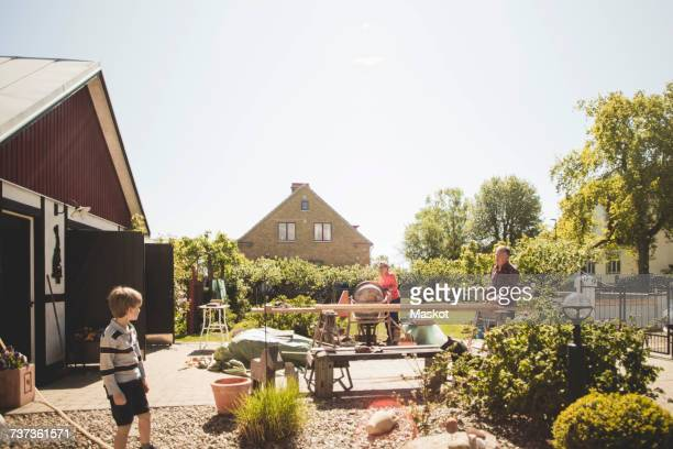 Boy looking at grandparents doing carpentry in yard against clear sky