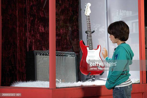Boy (7-9) looking at guitar in shop window, side view