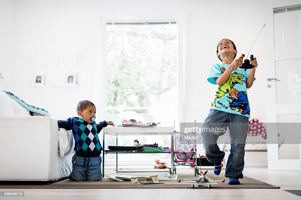 Boy looking at happy brother holding remote of model airplane at home : Stock Photo