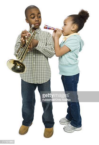 Boy looking at his sister blowing a party horn