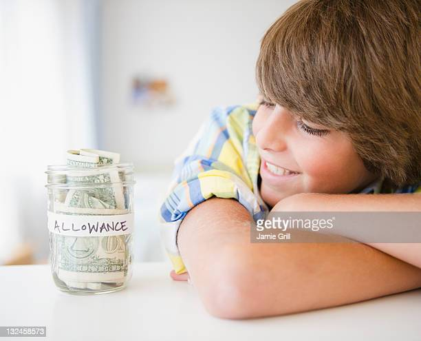 Boy looking at jar of money labeled allowance