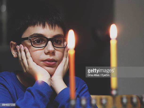 Boy Looking At Lit Candles On Hanukkah Menorah