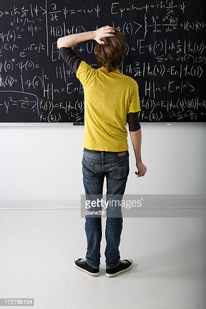 Boy looking at math problem on blackboard