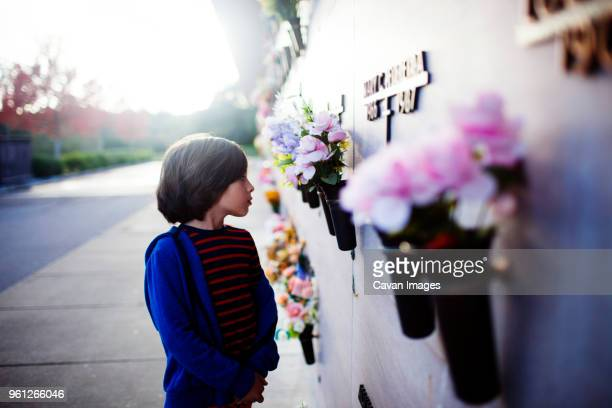 boy looking at memorial wall while standing at sidewalk - cemetery stock pictures, royalty-free photos & images