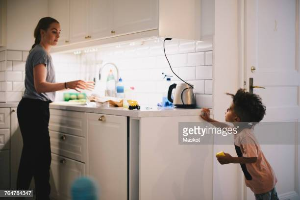 boy looking at mother working in illuminated kitchen - stay at home mother stock pictures, royalty-free photos & images