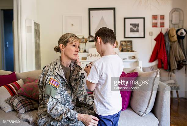 boy looking at mother's dog tags - military dog tags stock pictures, royalty-free photos & images