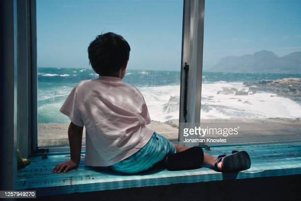 boy looking at ocean view - looking through window stock pictures, royalty-free photos & images