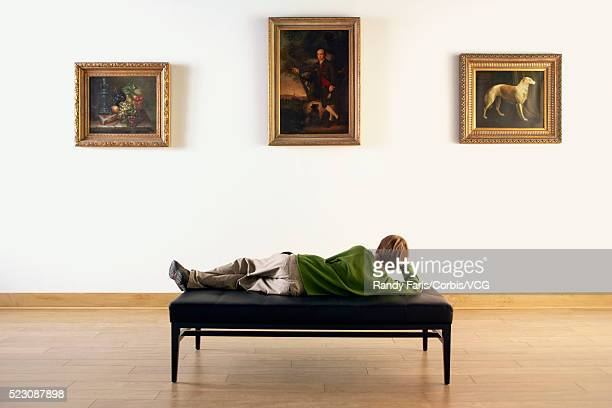 Boy Looking at Paintings in Art Gallery