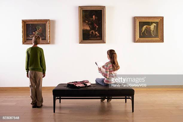 Boy Looking at Paintings in Art Gallery While Girl Sketches