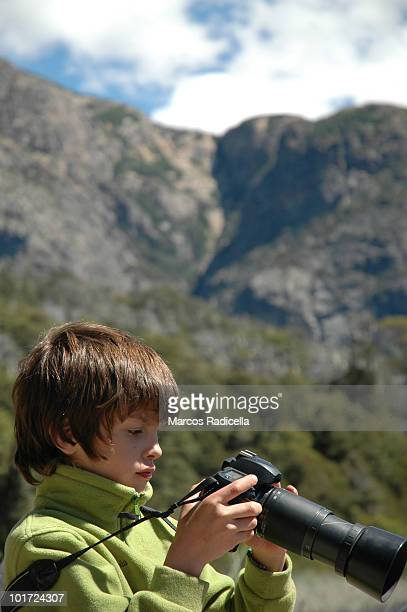 boy looking at photos on a camera - radicella stock pictures, royalty-free photos & images