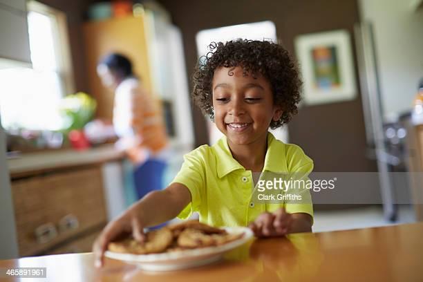Boy looking at plate of cookies